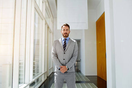 day break: Young man serious banker dressed in luxury suit with confident look is posing for camera during break in work day. Male professional architect is standing in hallway office building which he designed