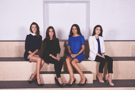 formal wear: Group of smarts female office workers dressed in formal wear are resting after conference with boss. Young attractive women are posing in modern interior after lectures in economics at Business School Stock Photo