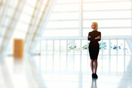 company premises: Confident businesswoman is standing in bought empty office space while is thinking about furnishings. Young beautiful female is standing with crossed arms in modern skyscraper interior with copy space
