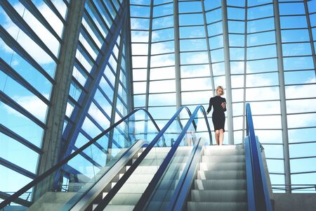 searching information: Young businesswoman is searching information on website via cell telephone,while is standing near escalator staircase in modern airport interior with contemporary building design Copy space background Stock Photo