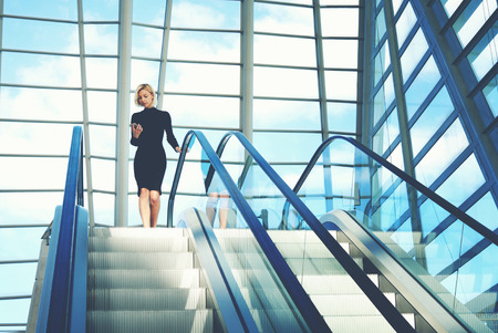 phone message: Businesswoman is reading financial news on web page via cell telephone, while is going to work break on moving staircase of big skyscraper office. Woman is reading message on phone and use escalator Stock Photo