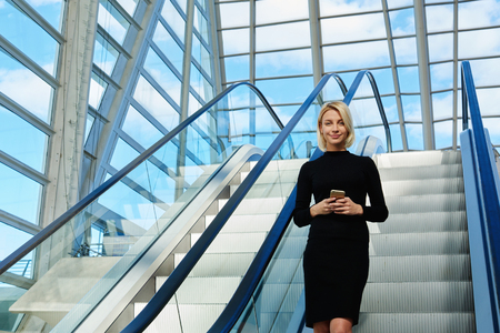 good mood: Young beautiful businesswoman is holding mobile phone, while is standing in office interior on moving staircase. Charming hipster girl in good mood with mobile phone in hands is standing in airport
