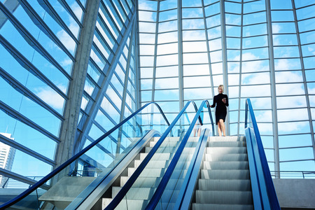 woman dialing phone number: Female skilled CEO is dialing a number on mobile phone while is standing near escalator in interior with contemporary design. Woman is using cell telephone, while is moving on staircase in office Stock Photo