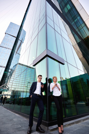 ceos: Two business worker are searching needed for briefing information on web page via mobile phones, while are standing outdoor against tall skyscraper building background with copy space for your content Stock Photo