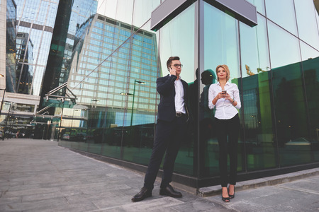 ceos: Young man boss in suit is having cell telephone conversation, while is standing with female partner outdoors. Blonde woman is holing cellphone in hands, while her boss is talking via mobile phone Stock Photo