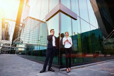 ceos: Man CEO is calling via mobile phone, while his female worker is thinking what to write in text message on cellphone. Two entrepreneur is using their cell telephones, while are waiting partner outdoors Stock Photo