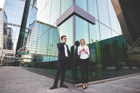 ceos: Businessman is calling via cellphone, while his secretary standing near with mobile phone in hands. Two smart managers are using their cell telephones during work break, while are standing outdoors