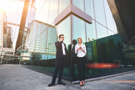 ceos: Confident man lawyer having mobile phone conversation, while his woman colleague is searching information on web page via cellphone. Two office workers are using cell telephones during break at job