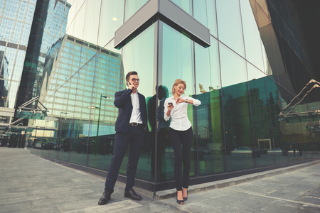 checking time: Man intelligent economist is phoning via cell telephone, while is standing with partner outside the company where they work. Blonde female is checking time, while her boss is talking on mobile phone Stock Photo