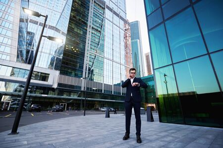 financier: Serious man manager is talking on mobile phone with customer, while is standing outdoors near office building where he work. Proud male financier is checking time during cell telephone conversation