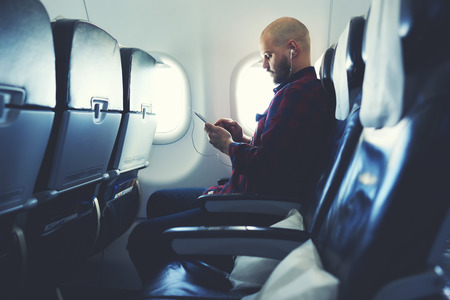 Man is listening to music in headphones and chatting in social network via mobile phone, during his flying in an airplane. Hipster guy is watching video on cell telephone , while is sitting in plane Stock Photo