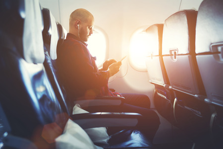 business trip: Man entrepreneur is watching video on mobile phone, while is sitting in plane near window with sun rays during his business trip. Hipster guy is listening to music in headphones via cell telephone Stock Photo