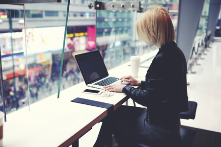 Stylish hipster girl is using for remote freelance job portable net-book during her vacation in China.Female student is searching information in internet via laptop computer during rest after shopping