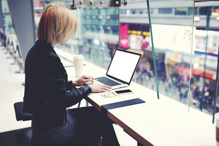searching information: Female successful businesswoman is using for distance work laptop computer with empty copy screen for your advertising text message. Hipster girl is searching information on web page via net-book Stock Photo