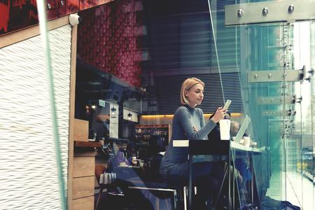 女性は、ビデオを見て、携帯電話を介して web ページにしばらくの間は近代的な流行に敏感なカフェに座っています。女性はファッションのニュース