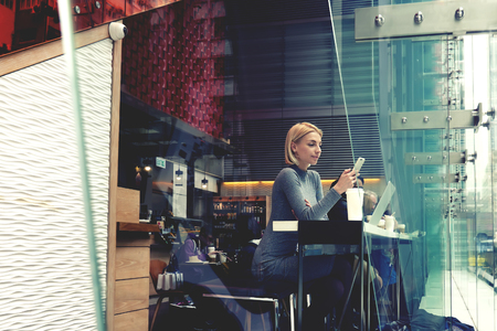 Woman is watching video on web page via cell telephone, while is sitting in modern hipster cafe. Female is reading fashion news in internet via mobile phone, while is resting her order in coffee shop