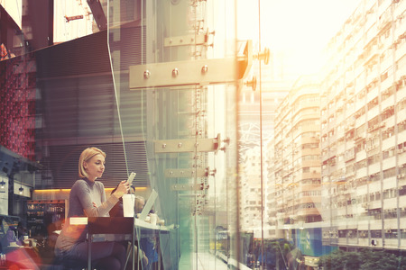 Young businesswoman is reading e-mail on cell telephone, while is sitting in modern coffee shop interior with large buildings outside the window and copy space background for your advertising content Banque d'images