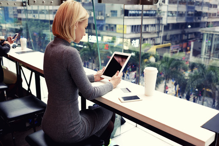 cell phones: Businesswoman is reading world news on touch pad with copy space screen for your advertising text message or content. Young female is watching video on digital tablet during rest in modern coffee shop
