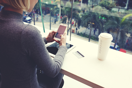 Closely of woman is typing text message on cell telephone, while is resting in coffe shop of modern shopping center in Hong Kong. Young hipster girl is chatting in social network via mobile phone