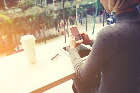 女性が携帯電話でおしゃべりですデジタル タブレットとテーブルでカフェに座っている、クレジット カード、コーヒーを奪います。女性が携帯電話