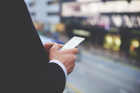 Gros plan des mains Man`s tient téléphone portable avec écran vide copie espace pour votre message texte publicitaire ou contenu promotionnel. Étroitement d'affaires rechercher des informations dans le réseau via un téléphone intelligent Banque d'images
