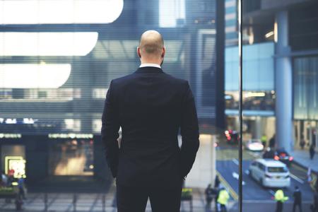 ビジネス旅行の間に国際的なパートナーとの重要な会議の後しばらくの間、休んでいる香港の中央通りで大きなオフィスの窓で高級スーツの CEO が見
