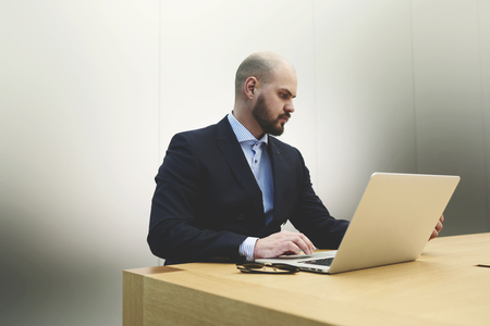 economic activity: Young male skilled financier is performing economic analysis of economic activity company on laptop computer. Successful businessman in suit is searching on net-book needed information for conference
