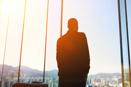 Silhouette of man managing director is examining the challenges the company after the refusal of investors in financing, while standing in evening time against office window background with copy space