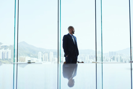financier: Serious man skilled financier is thinking about the crisis situations and methods of improving the situation, while is standing in modern office interior and watching in window on business district
