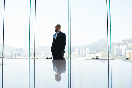 business lifestyle: Thoughtful man proud CEO is thinking about new methods of management of the construction company. Entrepreneur is watching in office window Honk Kong city with tall skyscrapers. Copy space background Stock Photo