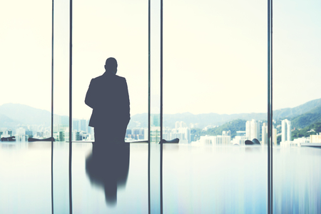 hard day at the office: Silhouette of a man jurist is resting after hard work day, while is standing in private office near window with view of business center in Hong Kong.Copy space background  for your advertising content Stock Photo