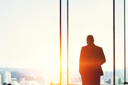 correctness: Silhouette of a man professional broker is thinking about the correctness of the decision before laying an agreement with buyer, while is standing near the window of a skyscraper with copy space