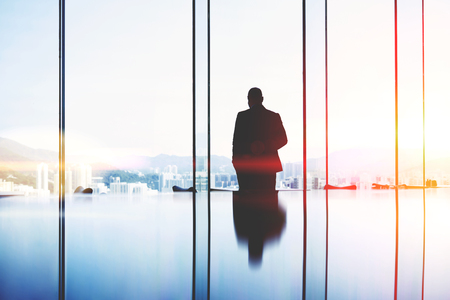 Silhouette of a man successful lawyer is thinking about the future of an important court session, while is standing in modern office interior near big window with view of developed Hong Kong city
