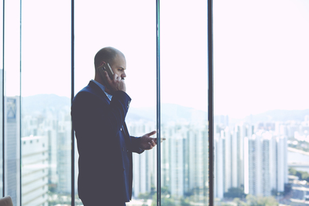 unsatisfied: Man owner of successful company in the field of real estate trade is having serious mobile phone conversation with unsatisfied customer, while is standing near window with view of metropolitan city