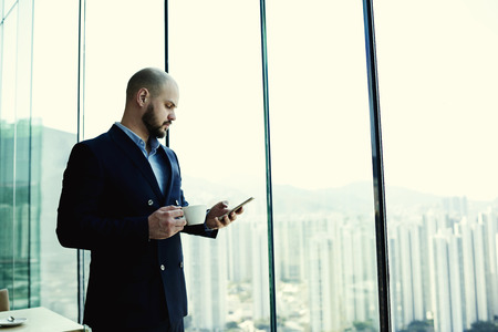 banking concept: Man skilled financier is reading financial news in network on mobile phone during coffee break in work day, while is standing in office interior near window with city view background and copy space