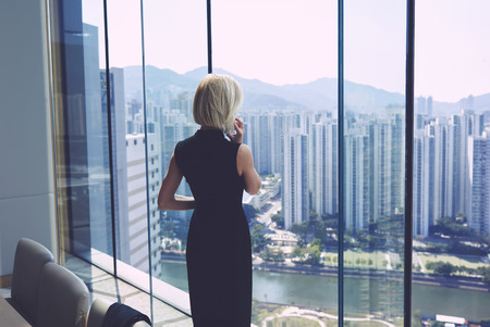 Back view of young successful businesswoman is having mobile phone conversation with managing director her company, while is standing in office interior near window with cityscape view and copy space Фото со стока - 59209182