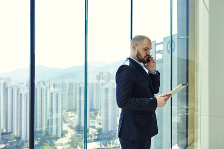 Young man serious managing director is calling to his manager to find out why he had not sent to e-mail on digital tablet reporting on implementation of work, while is standing near office window