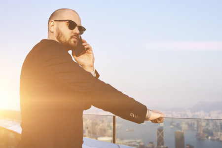 financier: Young skilled man financier in fashionable sunglasses having cell telephone conversation, while is standing on a roof tall skyscraper. Successful male CEO is calling via mobile phone during work break Stock Photo