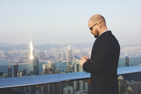 banking concept: Confident businessman is typing text message on mobile phone, while is standing on roof building against amazing view of a developed city with skyscrapers. Copy space background for your content Stock Photo