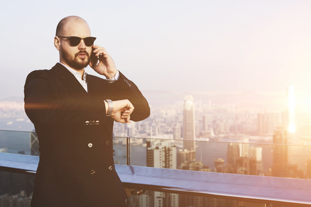 checking time: Young rich man in sunglasses is checking time on watches and talking on mobile phone,while is standing on a building roof against Hong Kong city with copy space background for advertising text message