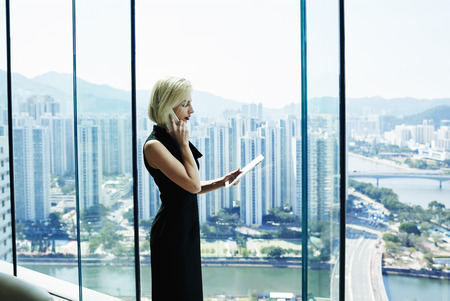 view to outside: Young woman successful manager of big thriving company having cell telephone conversation,while is standing with touch pad in hand against cityscape view outside office window.Copy space for content