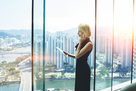 wealthy lifestyle: Young proud businesswoman is talking on her mobile phone with client and reading order on digital tablet, while is standing near office window with view of developed business district in China