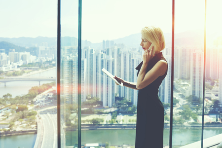 website window: Young successful female boss is talking on cell telephone with customer and read information on website via digital tablet, while is standing in modern office interior near window with cityscape view