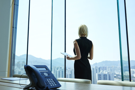 Woman proud CEO with digital tablet in hands thoughtful is looking into the office window, while is standing in skyscraper interior in big conference room with table. Copy space for advertising text
