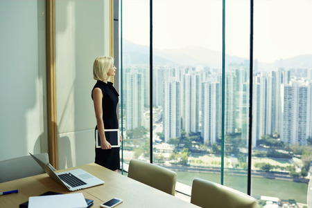 Thoughtful woman professional banker with touch pad in hand is watching in big office window with cityscape view,while is standing near meeting table with open laptop computer,phone and paper document Banco de Imagens
