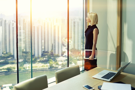 Woman skilled employer with touch pad in hand is looking in office skyscraper window of conference room while is thinking that adopt a decision after interview with specialists in the economic sphere Banque d'images