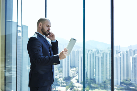 finance director: Serious businessman in luxury suit with digital tablet in hand dissatisfied with fall of quotations his shares on international stock exchanges is talking via mobile phone with his finance director Stock Photo
