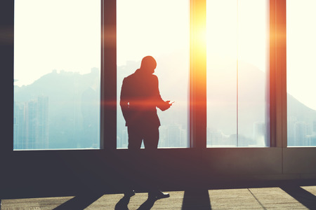 banking concept: Silhouette of man is watching video in network via mobile phone, while is standing in office interior against skyscraper window with sunset. Male manager is typing to partner text message on cellphone Stock Photo