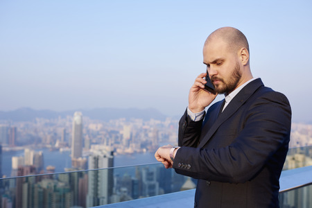 expects: Intelligent man jurist is checking time and calling via cellphone to client which he expects, while is standing on a tall skyscraper against developed Hong Kong city with copy space for your content Stock Photo