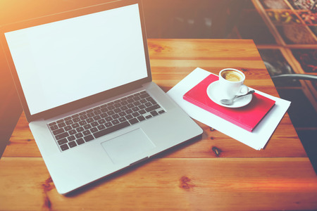 netbook: Open laptop computer with blank copy space screen for your information content or text message, portable net-book with cup of cappuccino lying on wooden table in contemporary coffee shop interior Stock Photo